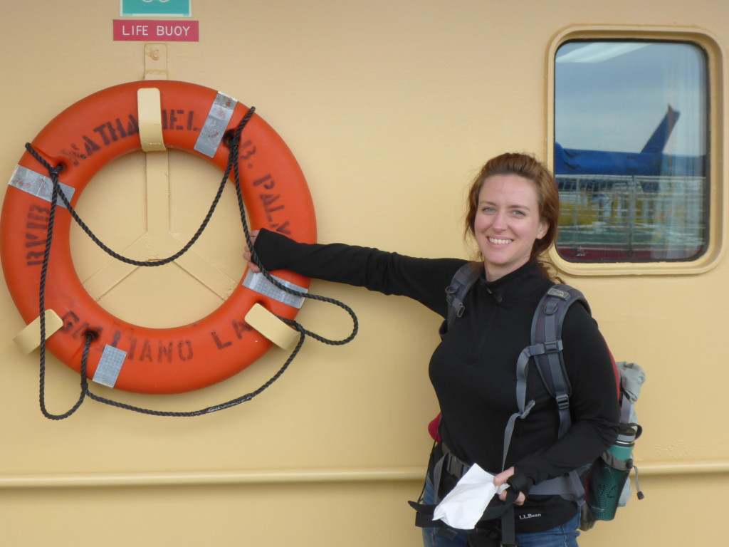 Image: Dr. Kerin Claeson stands on the deck of the Nathaniel B. Palmer, next to an orange life preserver ring. She is wearing a camping backpack and smiling broadly.
